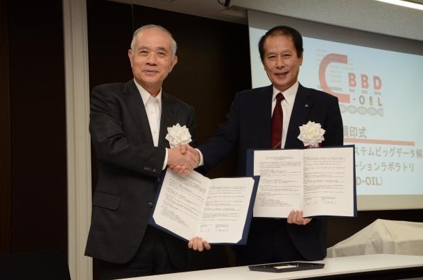 調印式後、握手を交わす産総研・中鉢良治理事(左)と早大・鎌田薫総長(右)