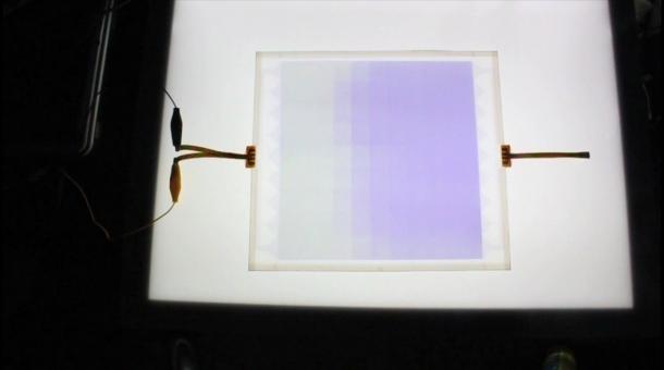 図4 グラデーション変化する調光ガラス(サイズ:20  20 cm)(左側が透明部分、右側が遮光部分)
