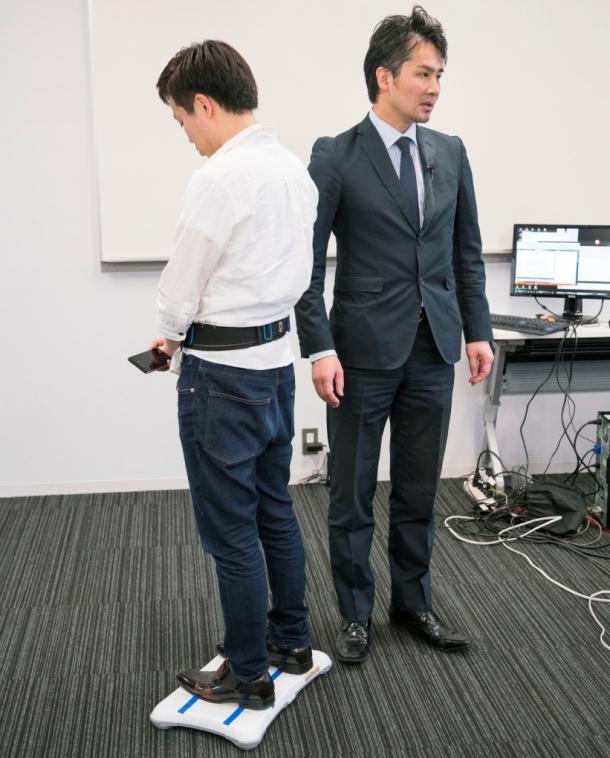 写真:バランス鍛錬ロボットテクノロジー。平衡感覚を鋭敏化するため腰に巻いたベルトへの振動で重心偏在を気付かせる。繰り返し訓練により、気づかないうちにバランス能力の向上が期待できる